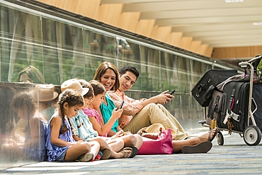 Family waiting on floor of airport using cell phones