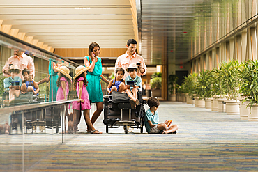 Family waiting in airport using cell phones