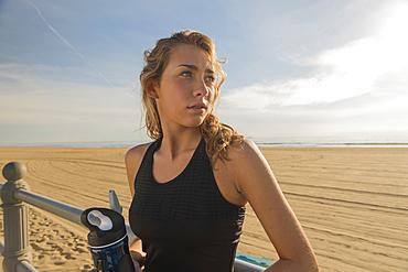 Caucasian teenage girl leaning on railing at beach