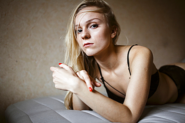 Close up of serious Caucasian woman resting on bed