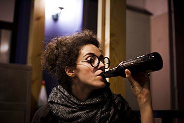 Caucasian woman drinking bottle of beer