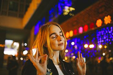 Caucasian woman listening to nightlife