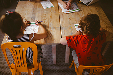Caucasian boy and girl sitting at table coloring