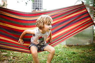 Caucasian boy sitting in hammock