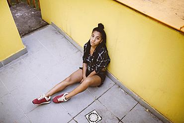 Portrait of serious African American woman sitting on sidewalk
