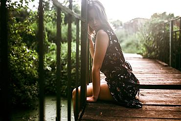 Caucasian woman sitting on wooden bridge