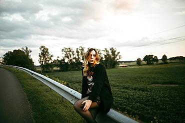 Caucasian woman sitting on guardrail near road