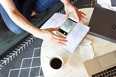 Caucasian woman photographing paperwork with cell phone