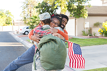 Black woman soldier hugging man and daughter