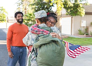 Man watching black woman soldier hugging daughter