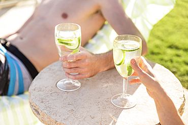 Caucasian couple relaxing in lounge chairs holding drinks