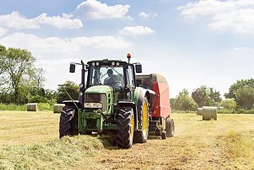 Caucasian man driving tractor baling hay