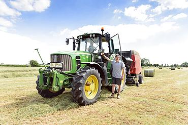 Confident Caucasian man standing near tractor