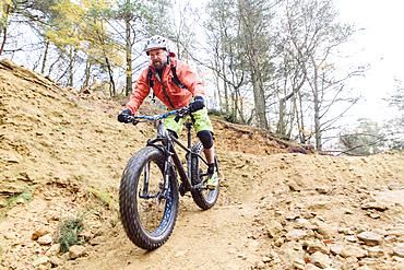Caucasian man descending dirt trail on bicycle