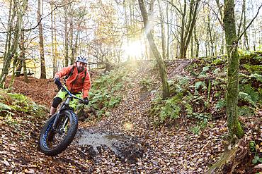 Caucasian man steering bicycle around mud puddle