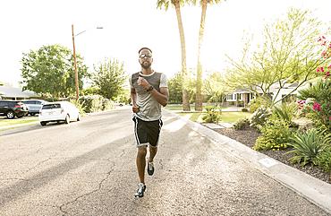 Black man running on street in neighborhood