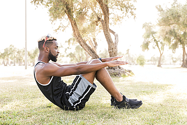 Black man doing sit-ups in park