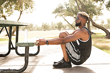 Black man holding picnic table in park stretching arms
