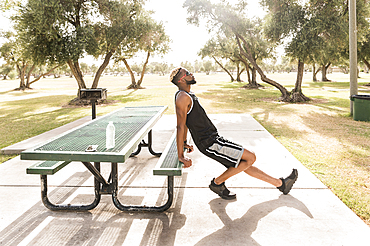 Black man leaning on picnic table in park stretching leg