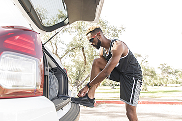 Black man leaning on car hatchback tying shoe