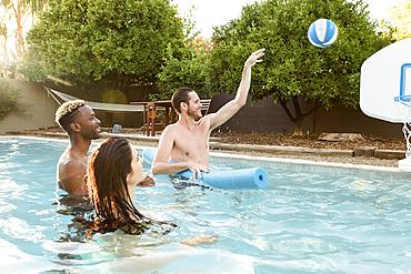 Friends watching man shooting basketball in swimming pool