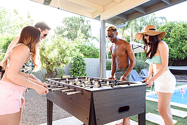 Friends playing foosball outdoors near swimming pool