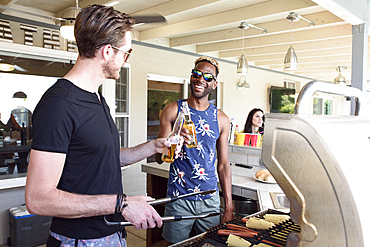 Men cooking on grille and toasting with beer outdoors
