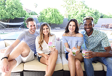 Portrait of smiling friends with cold drinks sitting outdoors