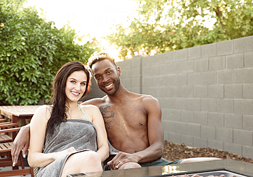 Portrait of smiling couple wrapped in towels near fire pit