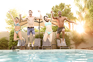 Friends holding hands jumping into swimming pool