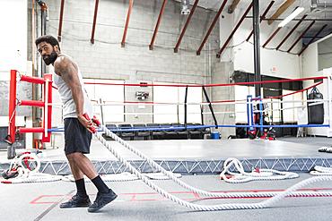Black man pulling heavy ropes in gymnasium