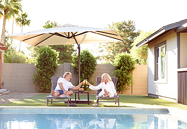 Caucasian couple toasting near swimming pool