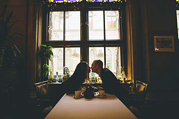 Caucasian couple sitting at table rubbing noses