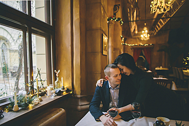 Caucasian couple drinking wine and hugging in restaurant