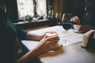 Hands of Caucasian couple drinking coffee and wine