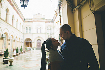 Caucasian couple standing face to face in courtyard