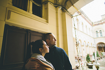 Caucasian couple hugging and leaning on wall in courtyard
