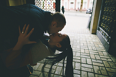 Caucasian man dipping and kissing woman