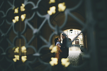 Caucasian couple embracing in street behind gate