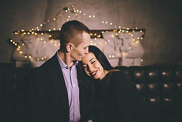 Caucasian man kissing forehead of woman
