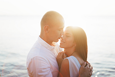 Caucasian couple hugging near ocean at sunset