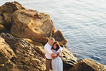 Caucasian couple hugging on rocks on beach