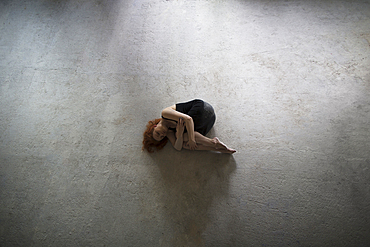 Caucasian woman laying on concrete in fetal position