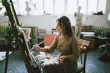 Serious Caucasian woman painting on canvas