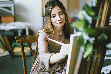 Caucasian woman painting on canvas