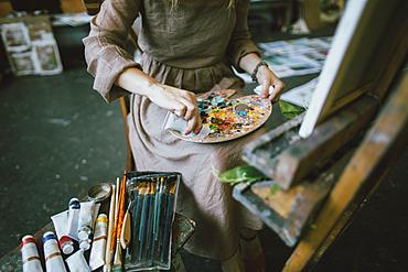 Caucasian woman squeezing paint onto palette