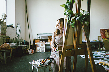Caucasian woman painting in studio