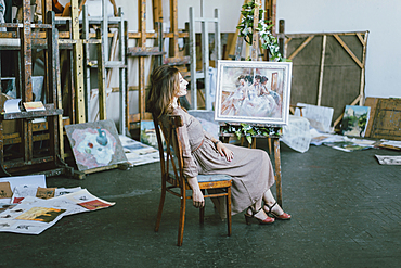 Caucasian artist sitting near painting on easel
