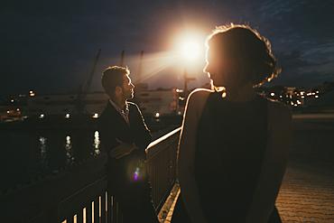 Caucasian man and woman at waterfront at night