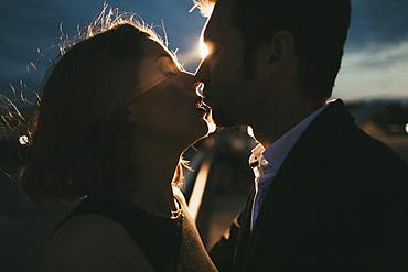 Caucasian couple kissing at night